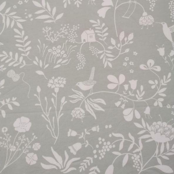 fondo verde suave y estampado en color blanco de pájaros, flores y hojas