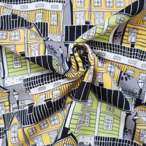 Fachadas de casas en tonos amarillos, blanco y verde con tejados negros.