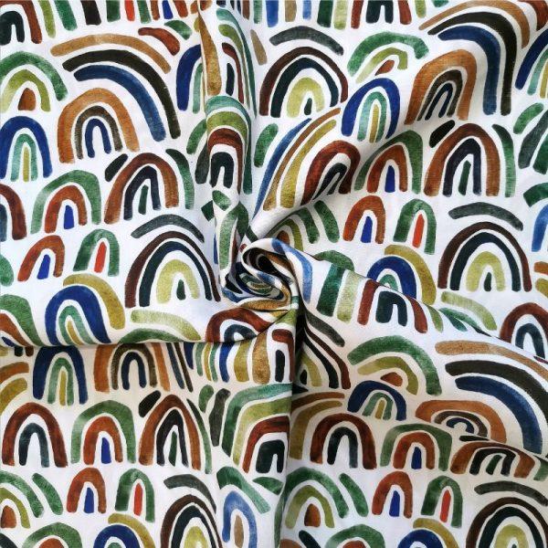 Fondo blanco con estampado de arcoíris multicolor, como pintados con acuarela. Tonos: verde, azul, mostaza, naranja.