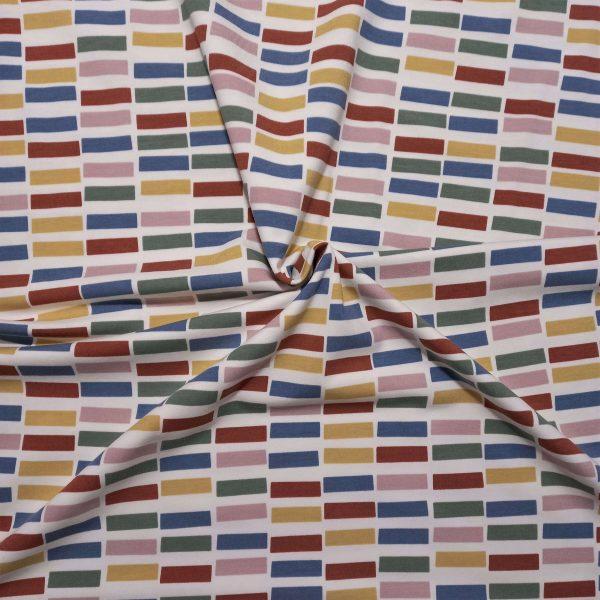 dibujo de ladrillos en muchos colores: teja, mostaza, verde, azul y rosa, sobre fondo rosa claro
