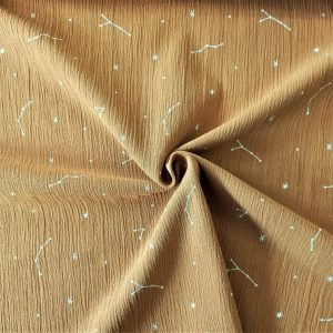 color mostaza, con un suave estampado en blanco de estrellas y constelaciones