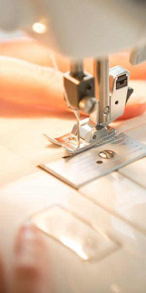 manos de mujer cosiendo a máquina
